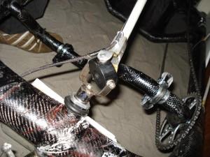 На фото изображена часть карбоновой пространственной рамы. Хорошо видно как реализован безкареточный цепной привод. Механизм в центре фотографии (кардан) соединяет переднее управляемое колесо и руль.